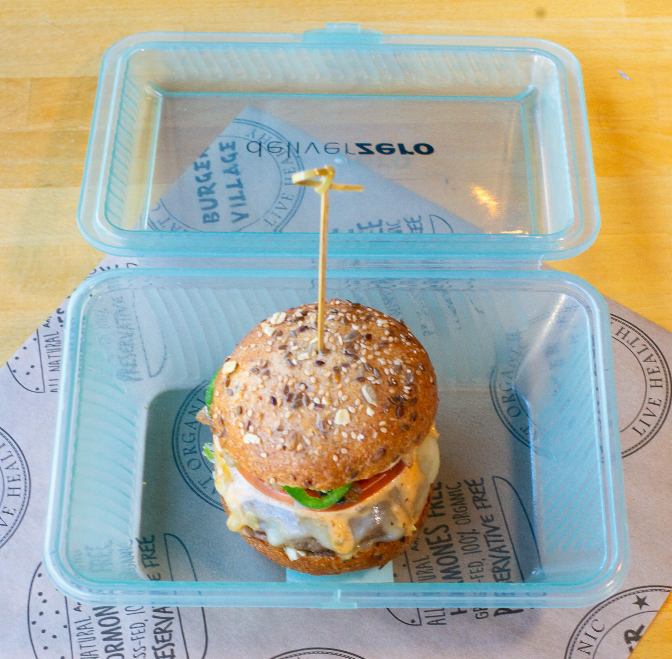A burger from Burger Village in a DeliverZero box.